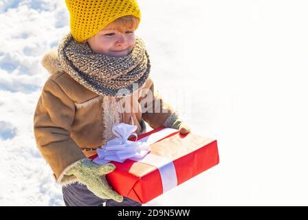 Enfant en vêtements d'hiver tient cadeau de Noël. Enfant lors d'une promenade dans un parc hivernal enneigé. Belle nature d'hiver. Parc d'hiver incroyable. Adorable enfant avec Banque D'Images