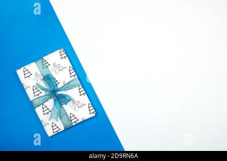Cadeau de Noël emballé dans du papier avec des imprimés de Noël et attaché avec un ruban noir. Boîte cadeau de Noël sur fond blanc Banque D'Images