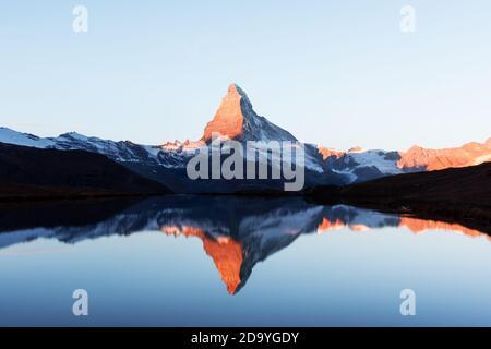 Paysage pittoresque avec le lever du soleil sur le lac Stellisee colorés. Snowy Matterhorn Cervino en crête avec reflet dans l'eau claire. Zermatt, Alpes Suisses