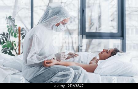 Femme médecin en blouse de laboratoire défensive et lunettes de protection avec seringue dans la main injectant des médicaments à la jeune fille malade de virus