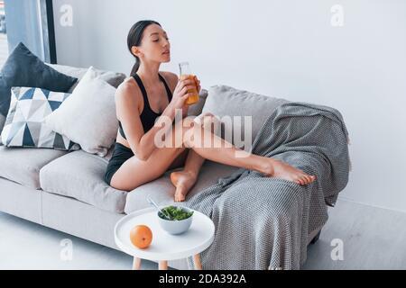 Une jeune femme au corps mince dans des vêtements de sport s'assoit canapé et mange des aliments diététiques sains à l'intérieur à la maison