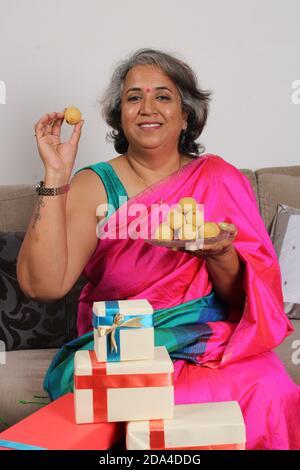 Femme indienne en saree / sari avec laddu et des boîtes cadeaux sur diwali / festival.