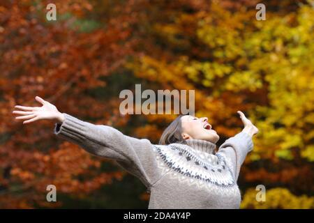 Femme excitée célébrant l'automne s'étirant les bras dans une belle forêt