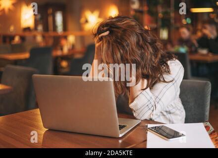 Femme brune adulte fatiguée en chemise à carreaux travaillant avec un ordinateur portable au café Banque D'Images