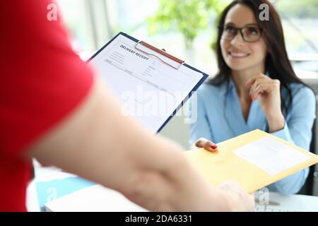 Le service de messagerie livre le courrier à une femme d'affaires à son bureau