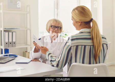 Le médecin de sexe féminin prescrit des médicaments et donne une ordonnance au patient.