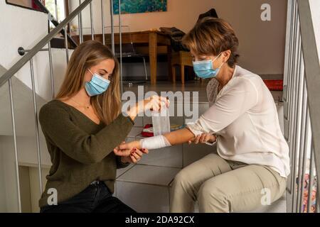 Premiers soins dans des conditions de corona, application d'un bandage, après un accident à la maison, avec un masque de nez et de bouche, lors de l'octroi de premiers soins