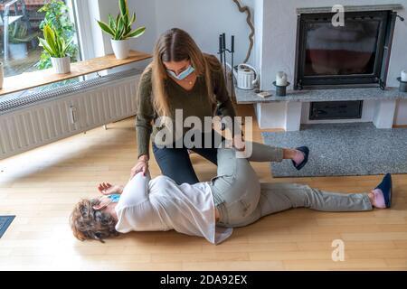 Premiers soins dans des conditions de corona, position latérale stable, après un accident à la maison, avec un masque buccal et nasal, lorsque les premiers soins sont à administrer