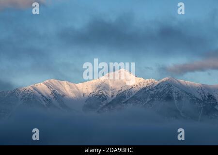 Le soleil se lève sur la pente est enneigée de Saddle Mountain, dans la chaîne de Lemhi, entourée de nuages le matin d'hiver.