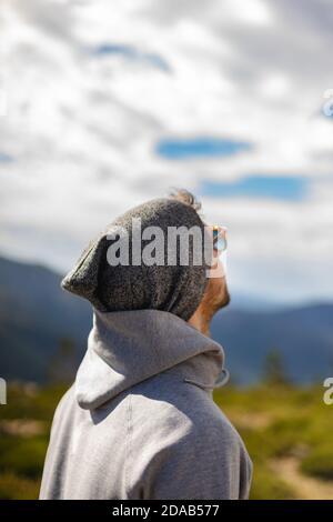 Jeune homme blanc de derrière avec des lunettes de soleil dans beau naturel cadre entouré de montagnes qui surplombent un ciel nuageux Banque D'Images