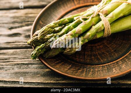 Les asperges vertes fraîches sur fond de bois