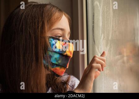 Petite fille européenne portant un masque de protection. Enfant malade petites filles regardent la fenêtre avec le désir sur la rue. Tristesse enfant à la maison dans isolati