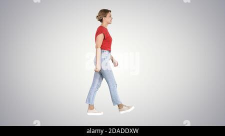 Femme en t-shirt rouge, jeans et baskets marchant sur un bac dégradé