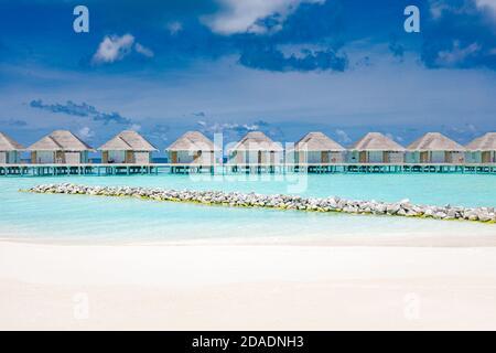 Villas aquatiques sur l'île paradisiaque tropicale, Maldives. Plage avec casiers et sable blanc. Destination de vacances d'été de luxe. Paysage de plage reposant