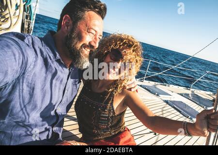 Heureux adulte couple caucasien ensemble sur un voilier profiter de vacances ou d'excursion - les gens en plein air activité de loisirs sur le bateau avec bleu océan et le ciel autour. Bonheur et amour homme et femme