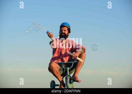 Mémoire d'enfance. Drôle d'homme sur un vélo pour enfants. Vélo nerdy.