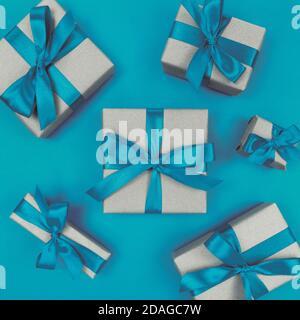 Boîtes-cadeaux emballées dans du papier artisanal avec des rubans et des noeuds bleus. Flat lay monochrome festif. Banque D'Images