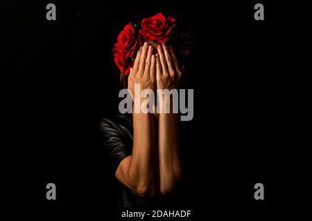 Jeune femme dans une couronne de fleurs, couvrant son visage avec ses paumes sur un fond noir.