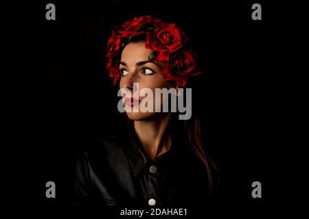 Jeune femme pensive dans une couronne de fleurs rouges sur fond noir.