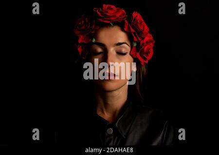 Jeune femme avec les yeux fermés dans la couronne sur fond noir.