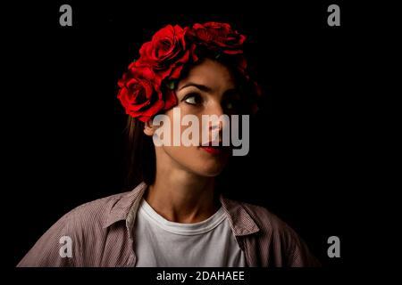 Une jeune femme dans une couronne de fleurs rouges regarde soigneusement sur le côté sur un fond noir.