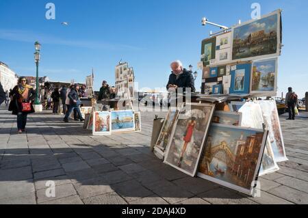 Les artistes vendent leurs peintures aux touristes sur la promenade centrale de la Riva degli Schiavoni (Slavyanskaya) par une journée ensoleillée à Venise, en Italie. Banque D'Images