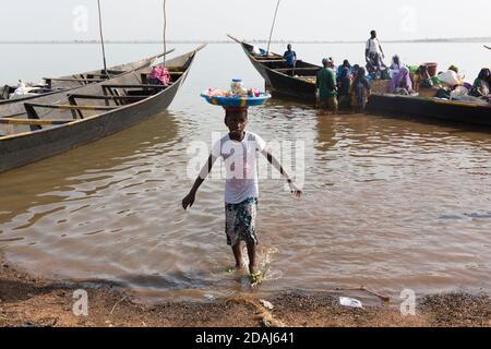 Selingue, Mali, le 25 avril 2015; Cariere village sur le lac barrage est un village de pêcheurs. Une jeune fille vend des bonbons aux passagers sur des bateaux qui les traverseront vers les autres villes du lac. Banque D'Images