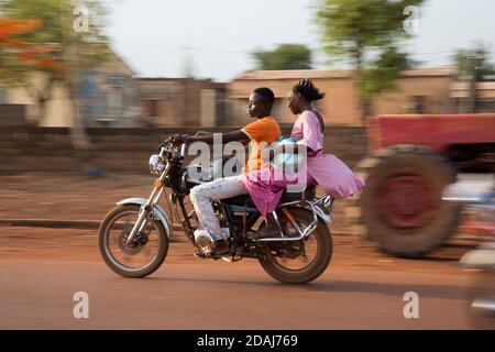 Selingue, Mali, le 25 avril 2015 ; les personnes en moto à la fin de la journée de marché. Banque D'Images