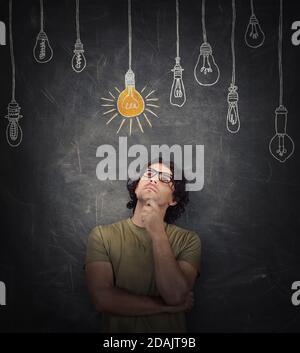 Le jeune homme pensif garde la main sous le menton, geste réfléchi, regardant focalisé, pensant aux idées géniales, en choisissant une ampoule incandescente