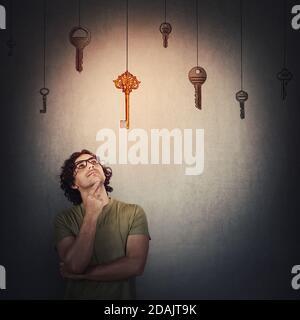 Le jeune homme pensif garde la main sous le menton, geste réfléchi, regardant vers le haut concentré, choisissant une clé dorée suspendue au lieu de multiples autres. Choïque droite
