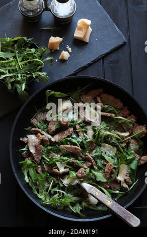 Stries de viande avec roquette et parmesan sur une casserole sur fond sombre. Vue de dessus.