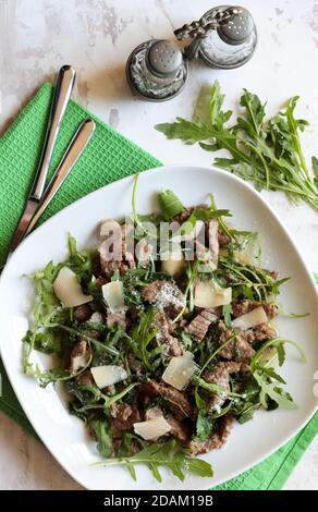 Stries de viande avec roquette et parmesan sur une assiette blanche. Vue de dessus.