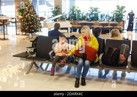 Jeune mère heureuse de jouer à un jeu avec sa fille à l'aéroport en attendant leur vol. Banque D'Images