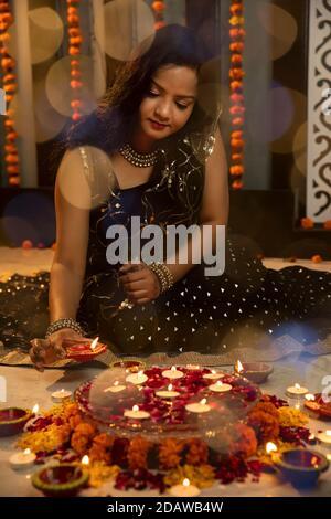 Portrait d'une femme indienne tenant des diyas et des lampes à l'occasion des fêtes de Diwali. Fêtes à la maison Banque D'Images
