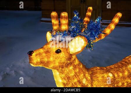Figurine cerf en acrylique clair, décoration de Noël renne illuminée dans le parc d'hiver de la ville.