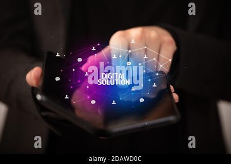 Businessman holding un smartphone avec l'inscription de la Solution numérique, nouvelle technologie concept