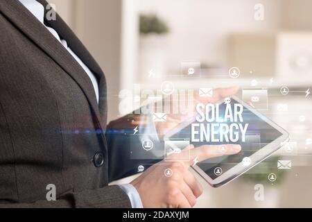 Gros plan d'une tablette à la recherche de l'inscription ÉNERGIE SOLAIRE, concept de technologie moderne Banque D'Images