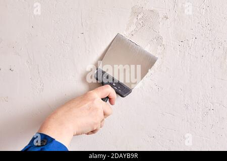 Le handyman remplit les trous dans le mur avec du stuc et un outil de travail.