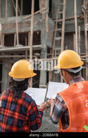 vue de l'arrière des entrepreneurs asiatiques hommes et femmes debout port de casques de sécurité tenant le bâtiment du plan du site dans le arrière-plan du bâtiment inachevé