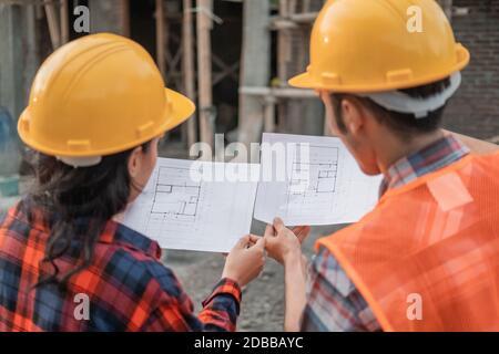 Vue de l'arrière de deux entrepreneurs asiatiques en sécurité casques tenant le bâtiment du plan du site en arrière-plan de le bâtiment inachevé
