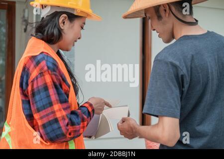 vue de l'arrière d'un constructeur féminin avec le doigt de pointage montrer des exemples de peinture à un constructeur dans une construction de bâtiment