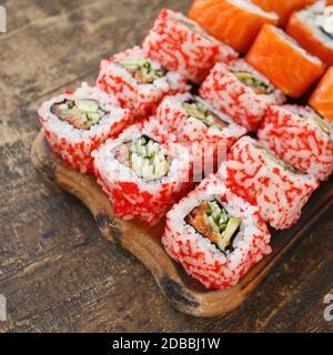 Deux sortes de rouleaux de sushi différents sur une planche en bois. Cuisine japonaise. Mise au point sélective