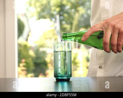 Homme d'âge moyen versant de l'eau dans un verre, concept de saine alimentation, propre et frais Banque D'Images