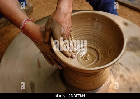 Poterie - mains humides et habiles de potter façonnant l'argile sur la roue de potter. Pot, vase jetant. Fabrication traditionnelle artisanat indienne bol, pot, pot