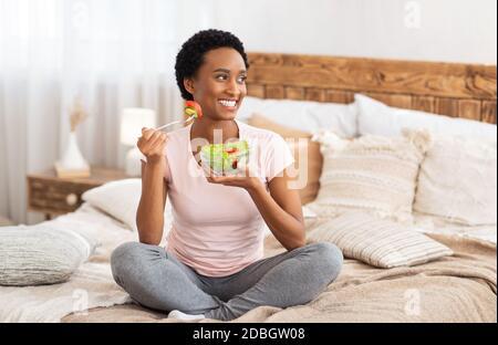 Régime alimentaire sain pour la perte de poids concept. Bonne femme noire mangeant de délicieux légumes salade sur le lit à la maison, espace vide