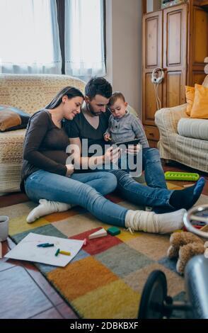 Famille avec enfant et femme enceinte à tablet
