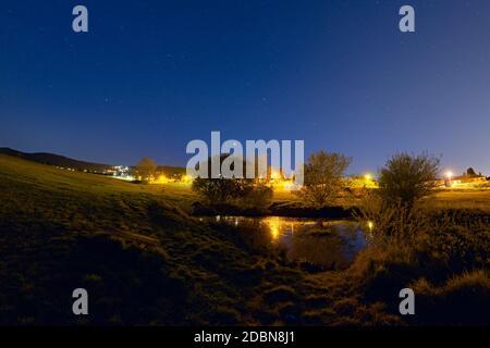 Avec les collines de Malvern en arrière-plan, un banc isolé donne sur un petit étang avec 4 arbres qui reflète le ciel étoilé bleu et les réverbères.