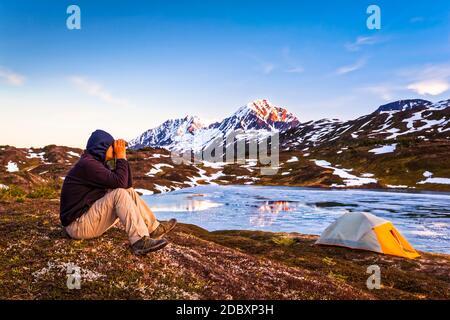 Un homme regardant avec des jumelles depuis le camp de Lost Lake au coucher du soleil. La résurrection culmine en arrière-plan. Forêt nationale de Chugach, péninsule de Kenai, Sud-
