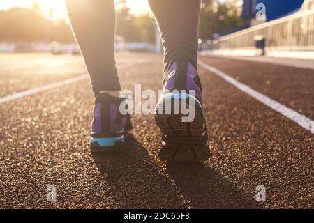 Les pieds de course sur les pistes du stade, à proximité de la chaussure. Femme fitness coucher de soleil jogging entraînement welness concept. Soleil sur fond.