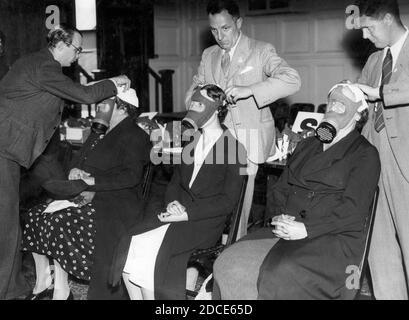 En 1939, trois femmes civiles sont installées pour leur propre masque à gaz personnel. L'Allemagne commençait à mener des actions de type guerre contre ses voisins. Vingt ans plus tôt, la première Guerre mondiale avait montré les horreurs du gaz toxique utilisé comme arme, et en Espagne des années 1930, des civils avaient subi des attaques au gaz par des avions. La Grande-Bretagne a compris qu'une attaque similaire de l'Allemagne serait dévastatrice pour sa population. À la fin de 1939, chaque homme, chaque femme et chaque enfant de Grande-Bretagne se faisait délivrer un masque à gaz. Pour voir mes autres images WW II, recherchez: Prestor vintage WW II